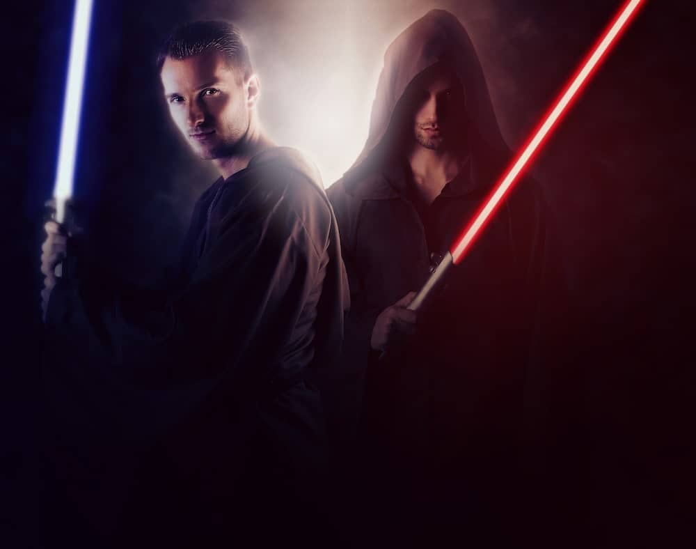 two men wield red and blue lightsabers
