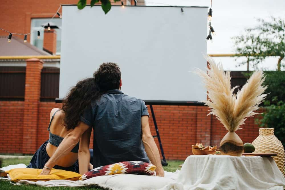 A young couple with an outdoor projector screen