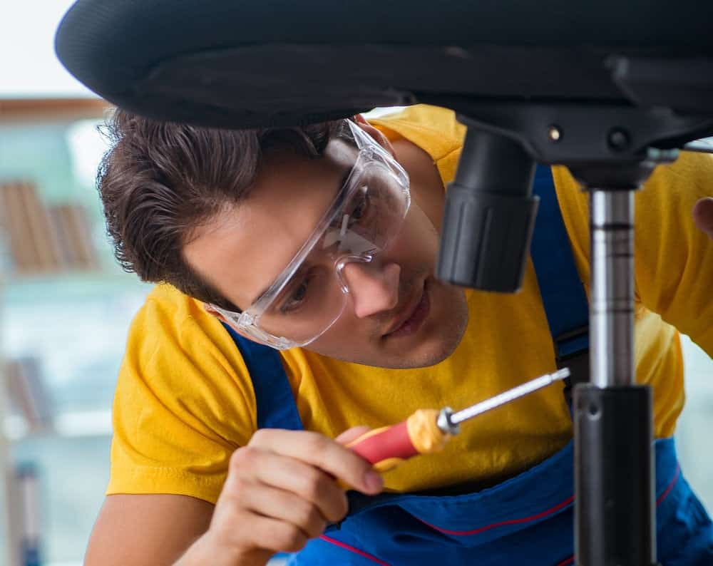 a young technician remove gas lift from a black office chair