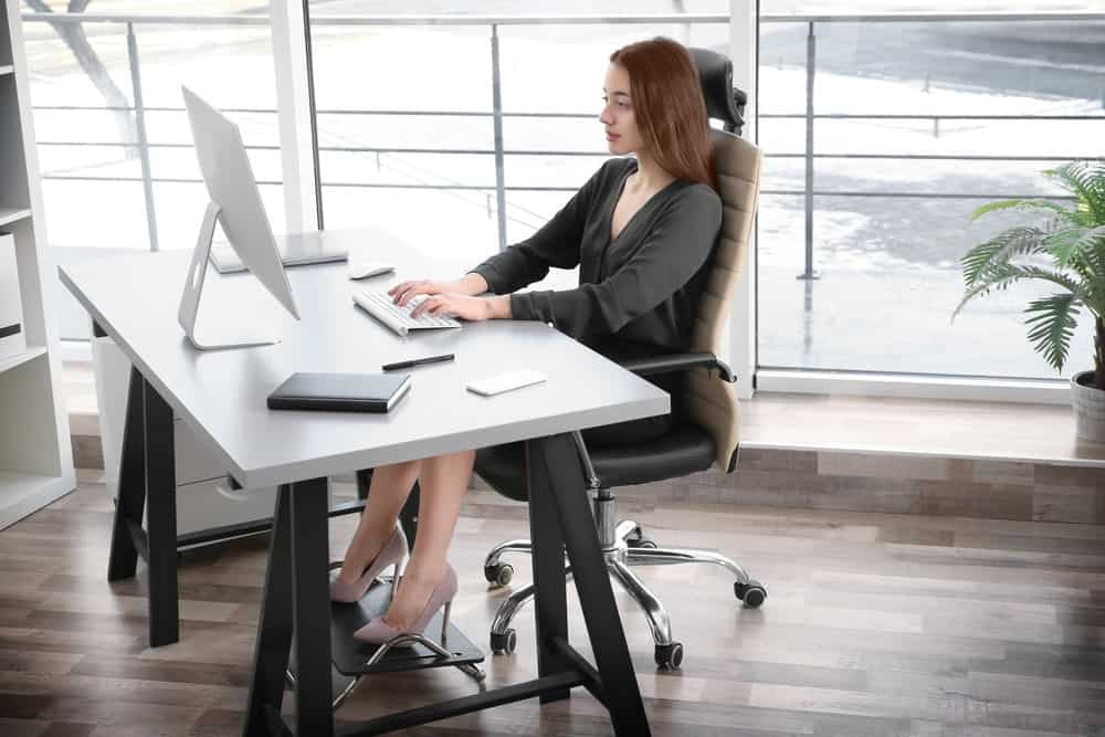 a women sitting at desk and using footrest