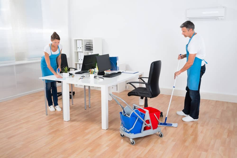 two cleaners clean vinyl chairs in office room