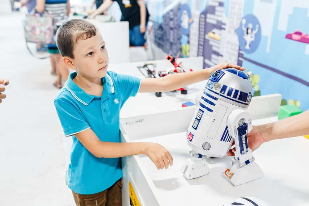 a kid buying R2-D2 Droid at Star Wars gift store
