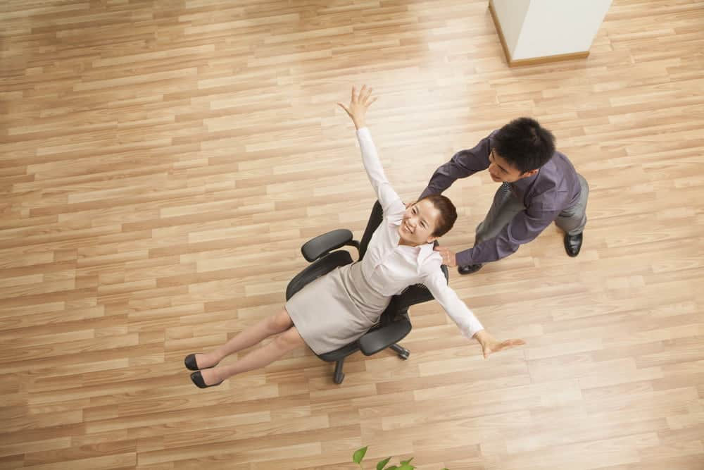 man push woman in office chair on the hardwood floor