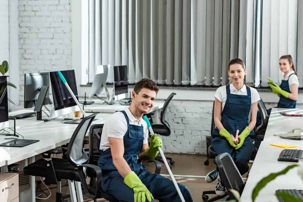 Team of young cleaners cleaning mesh office chairs