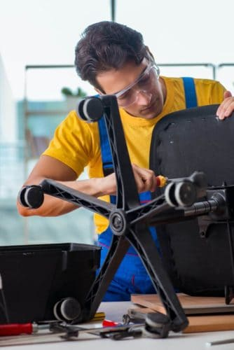 repairman removing office chair base