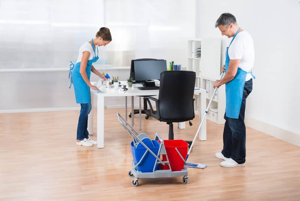 two janitors cleaning office chair