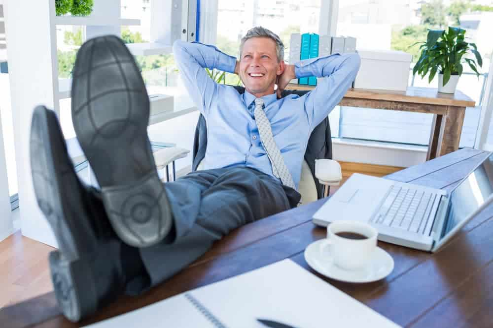 Businessman relaxing in a swivel office chair