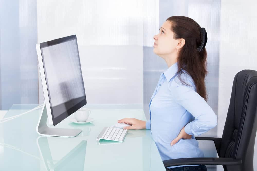 Businesswoman sitting long hours in office chair having back pain