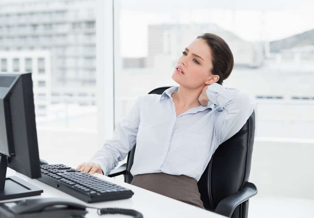 Businesswoman with neck pain sitting on office chair