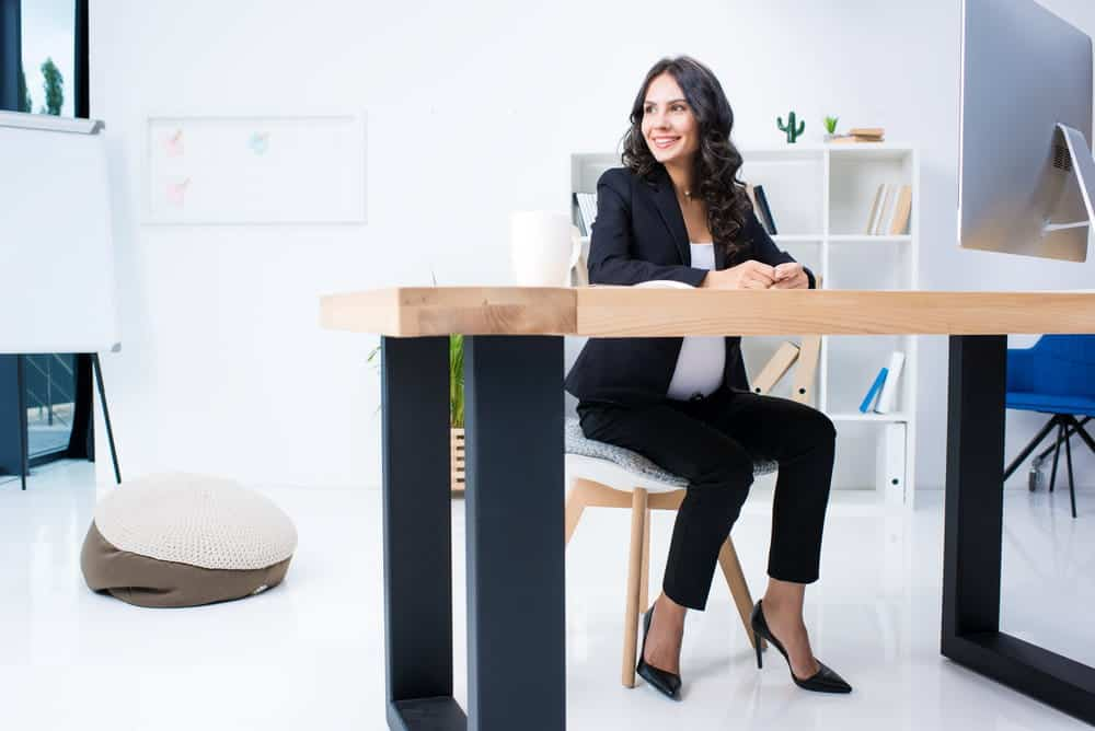 Pregnant businesswoman sitting comfortably in office chair at workplace