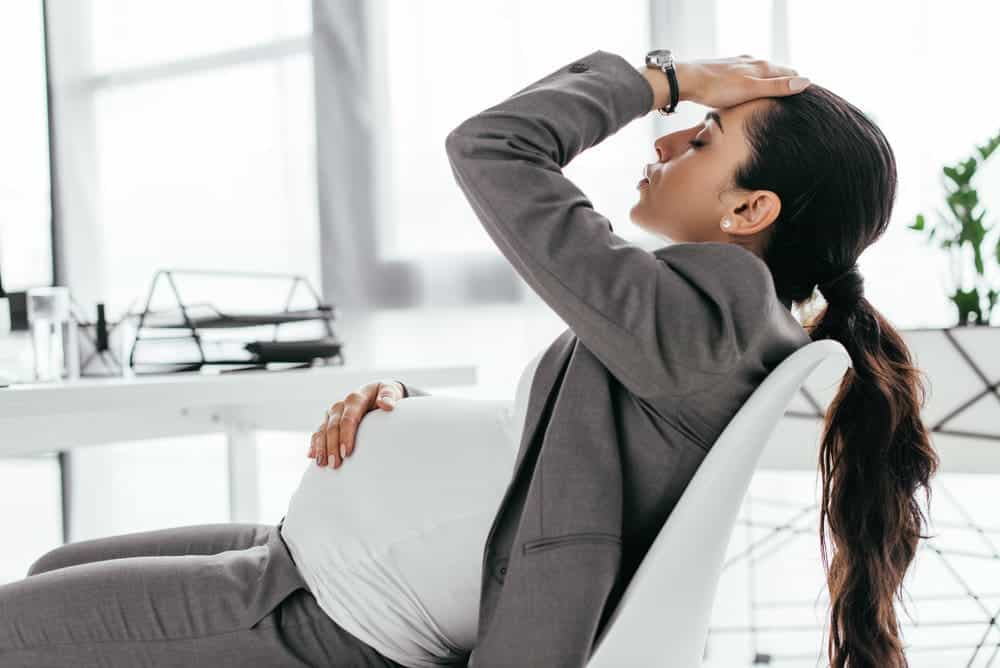 Tired pregnant woman sitting in office in chair