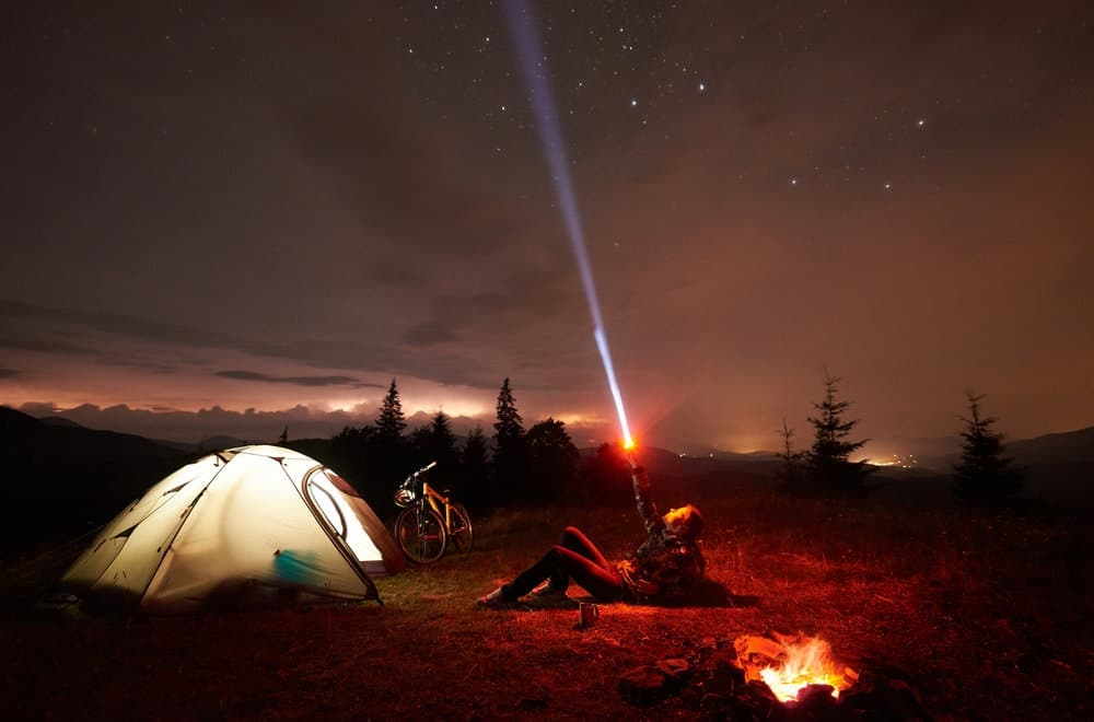 young woman using a high lumen flashlight to start a camping fire resting on a mountain alone