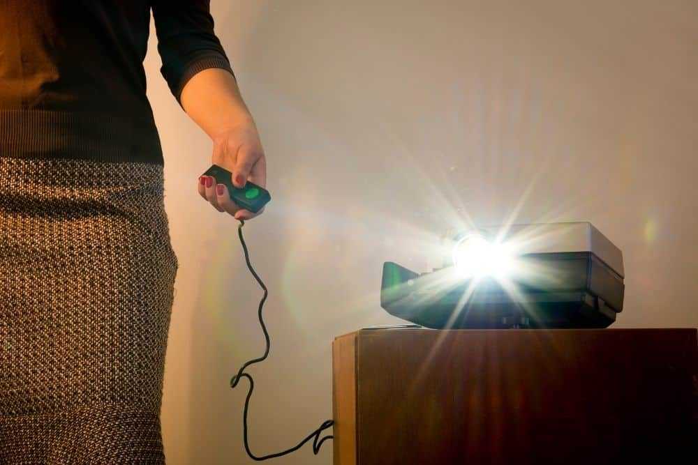 A Woman Test If The Projector Lamp Is Going