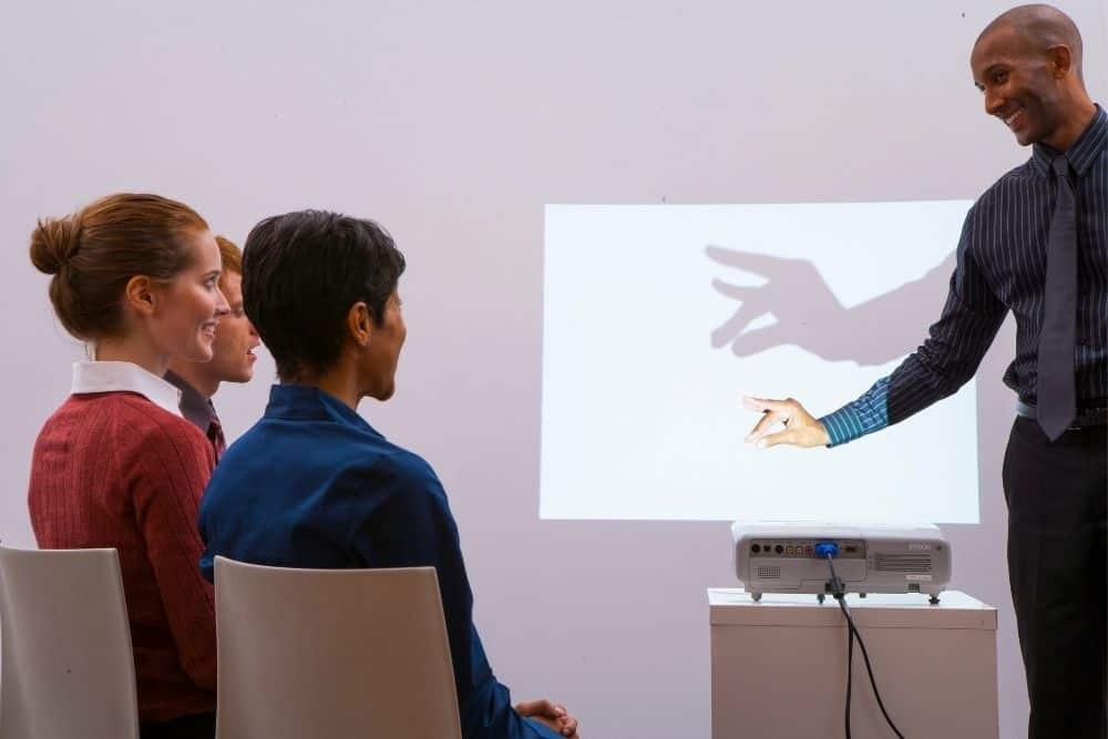 a professor playing shadow to check the projector lamp