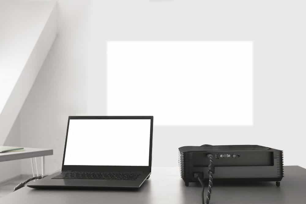 projecting image on white wall with a laptop and projector