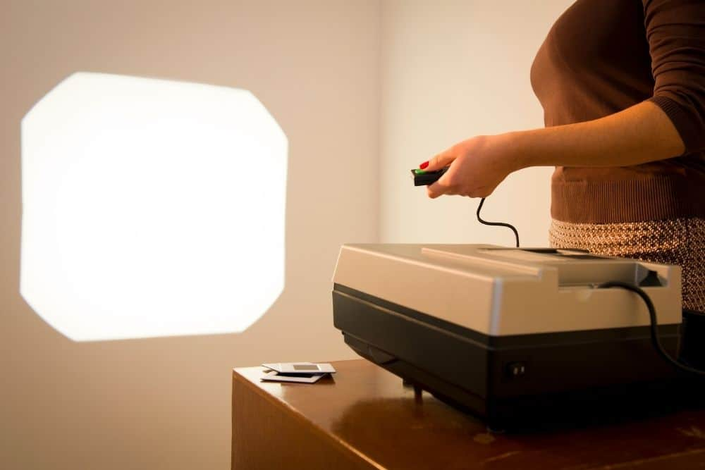 woman turning up the brightness of a projector lamp