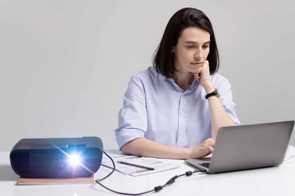 Woman Displays A Separate Screen On Computer And Projector