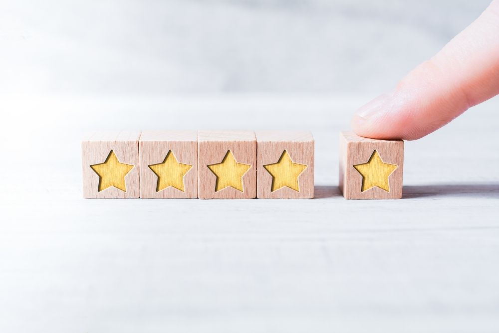a finger with 5 star ranking wooden blocks