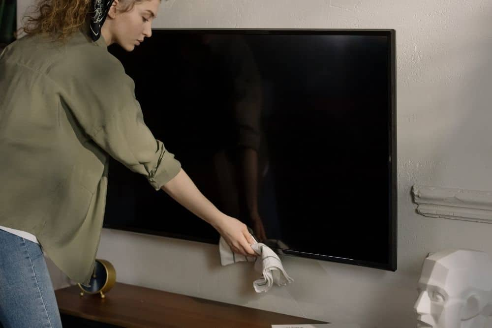 a woman cleaning the OLED TV