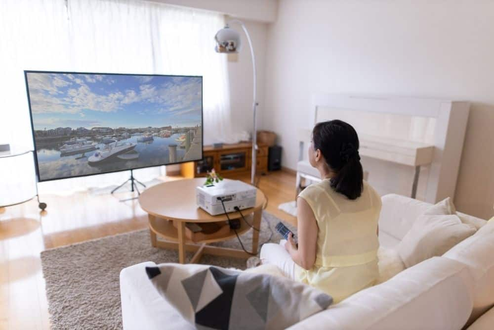 a woman watching 4k projector with high resolution image
