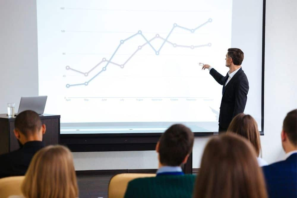 businessman using Pyle Widescreen LED Projector for presentation