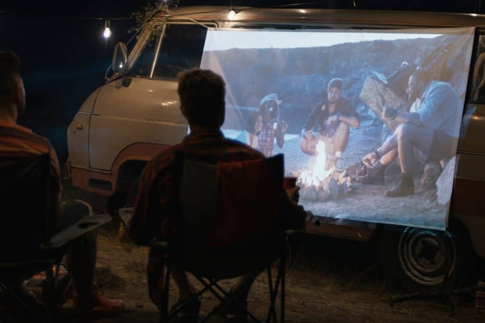 friends use a white sheet as a projector screen to watch movies in campsite