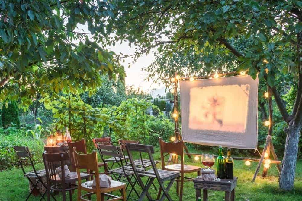 summer cinema in a garden with white sheet as a projector screen