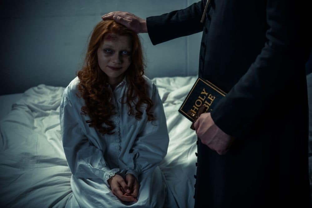 the exorcist holding bible and hugging demonic creepy girl in bedroom