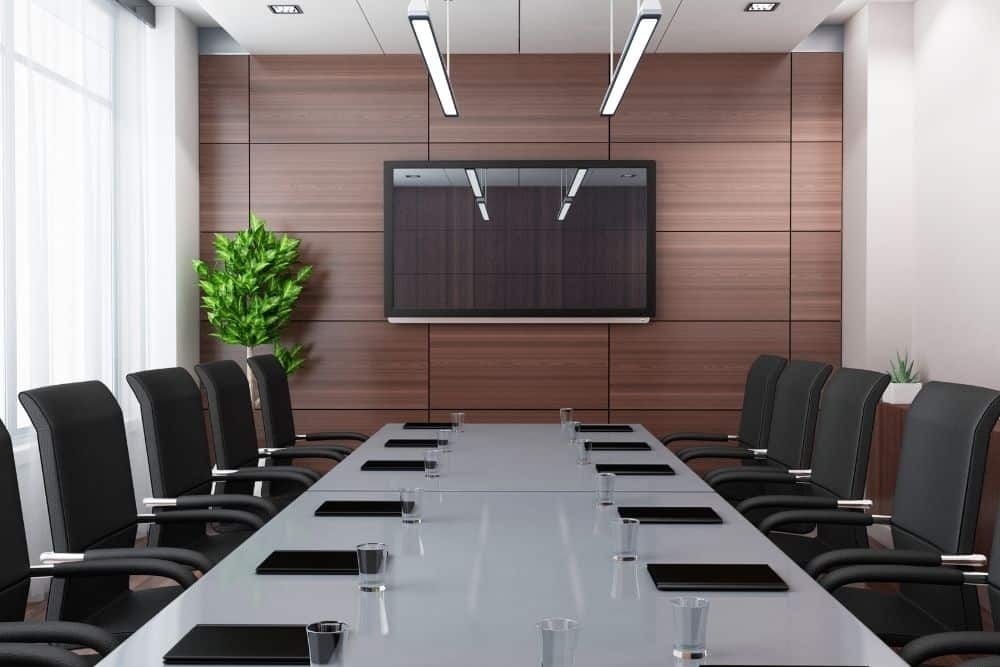a TV screen in a bright conference room