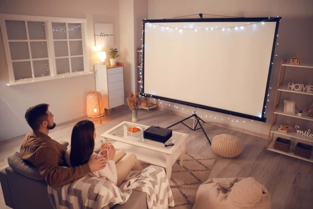 a couple watching movie with projector and projector screen in a room at night