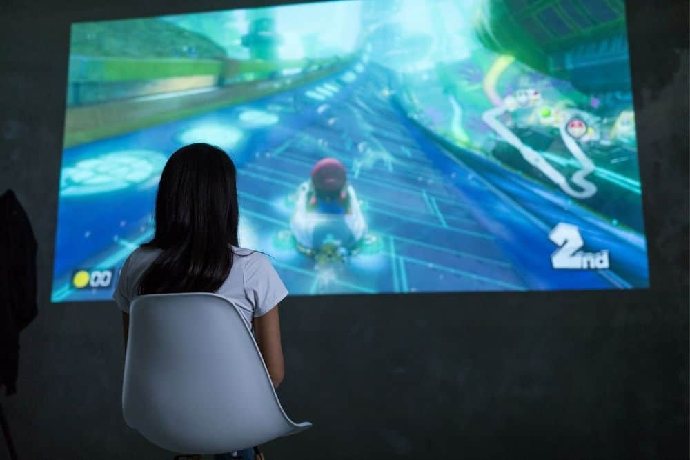 a girl playing Nintendo Switch on a projector