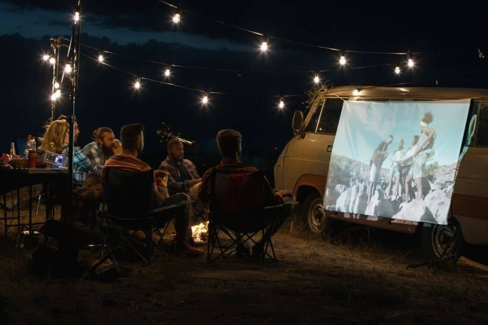 a group of friends watching movies with projector while camping