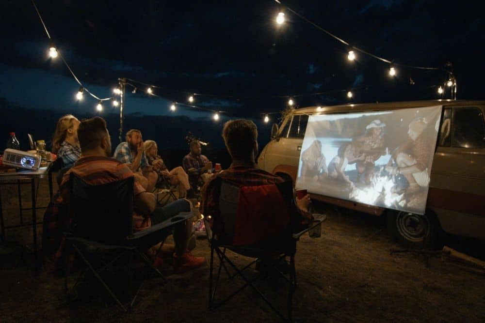 a group of friends watching movies with short-throw projector while camping