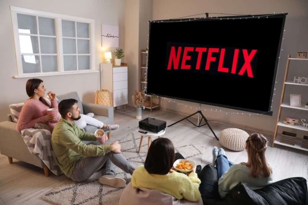 a group of people watching netflix with projector