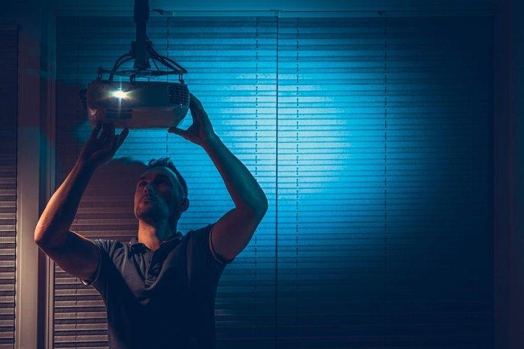 a man fixing a green projector