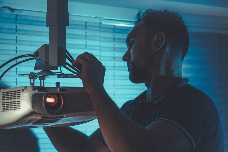 a man fixing projector