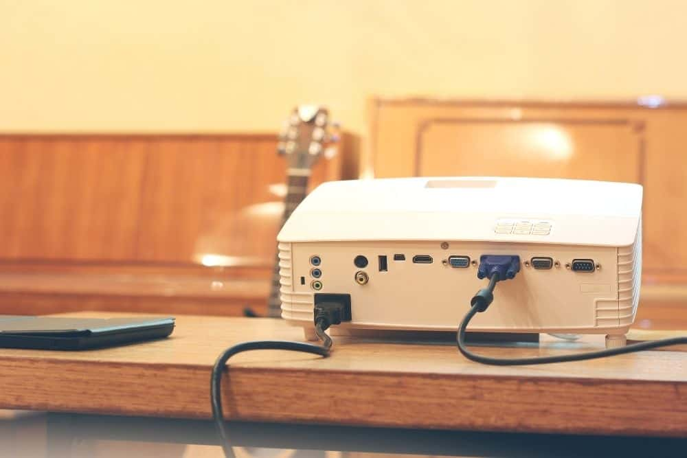 a projector on a table with VGA cable plugged in