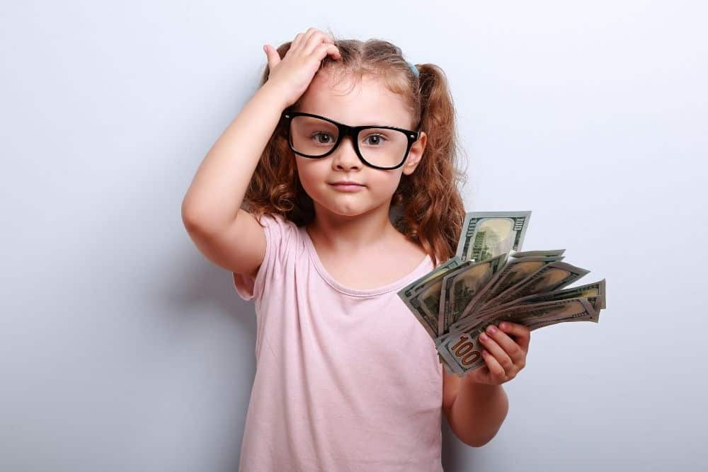 a small girl scratching head, holding money for buying Nintendo Switch