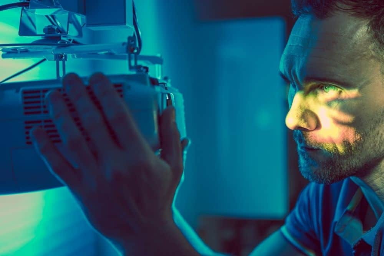 man fixing a new bulb of a dim projector