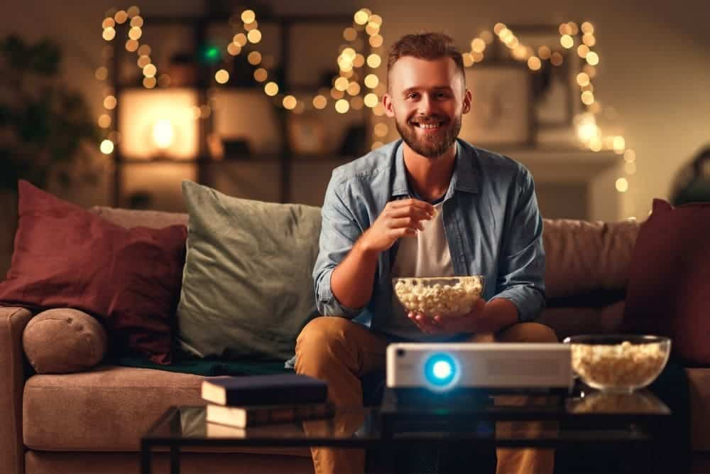 a man eating popcorn and watching movies with firestick connected to a projector
