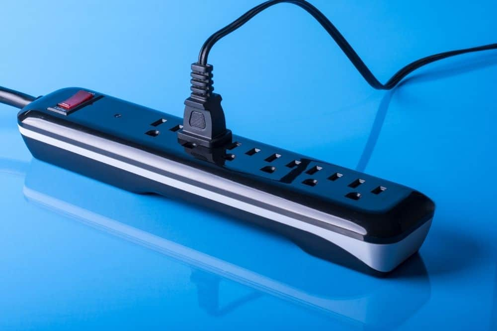 a surge protector with one projector plug on a blue background