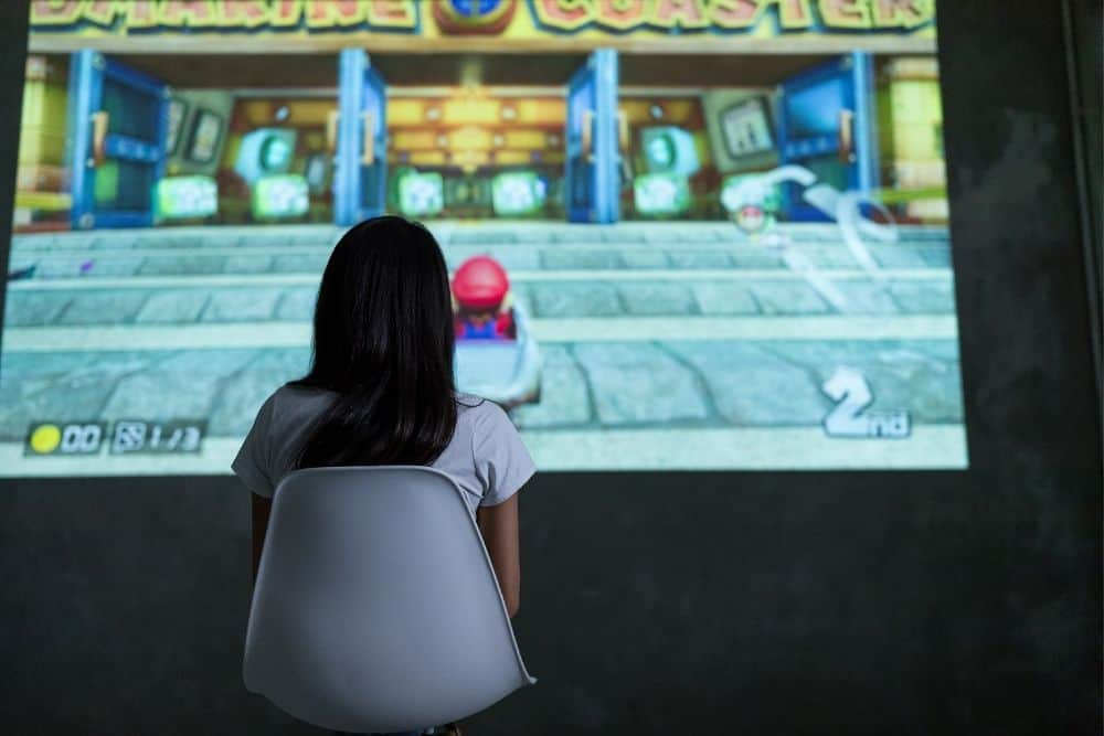 a girl playing Nintendo Switch with a projector