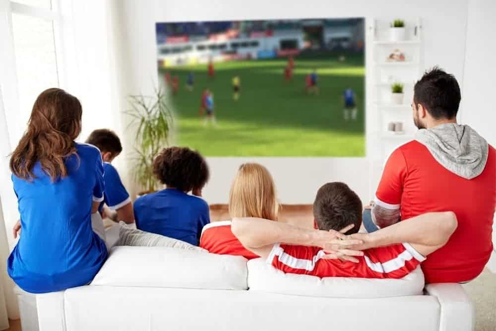 group of friends watching soccer with a projector displaying images in the wall