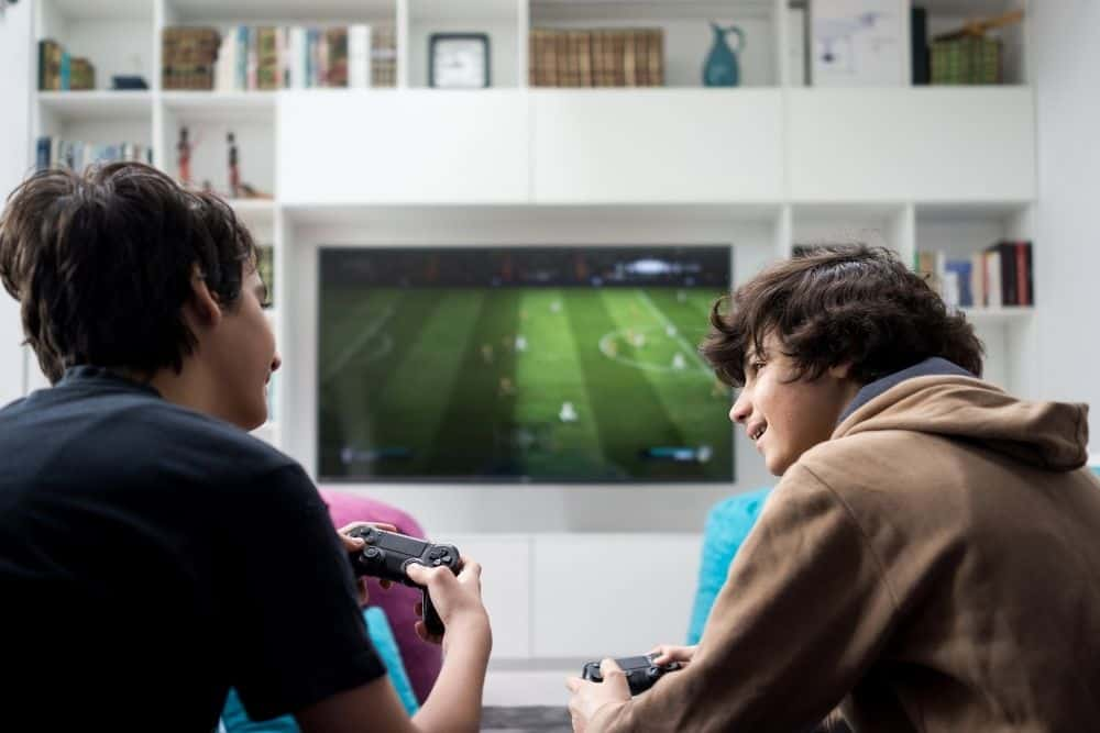 two friends playing games on a portable projector in a room