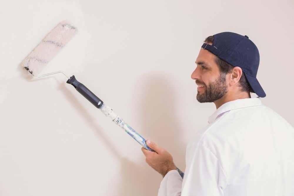 a man smiling and painting the wall projector screen white