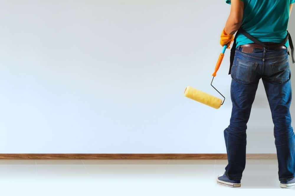 man standing in front of a large wall going to paint a projector screen