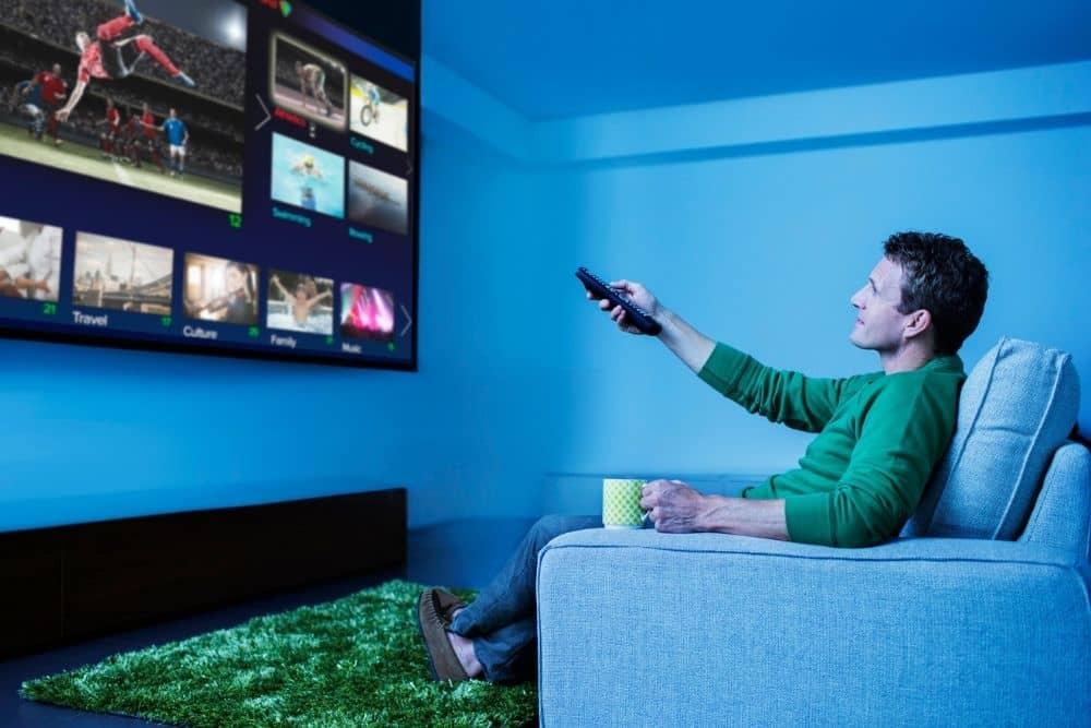 man watching flat screen TV