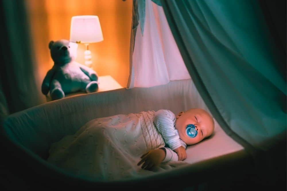 a baby sleeps in pink light