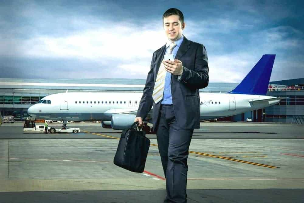 businessman holding a projector case travels by plane