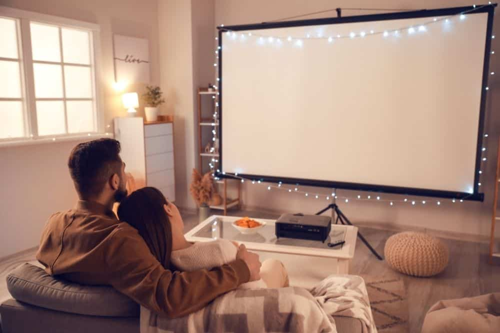 a couple using ultra short throw projector screen for movie night